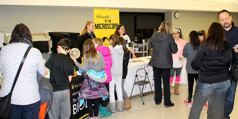 Biology students and faculty meeting with young visitors at an outreach event